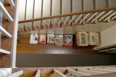 Stairway bird's eye view at Carl Sandburg's house of front hallway magazine piles (photo by Sheila Scarborough)