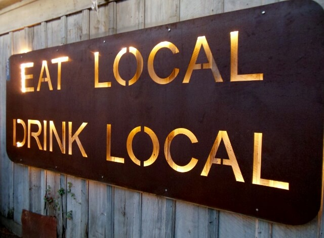Eat local drink local sign at Bastrop Brewhouse TX (photo by Sheila Scarborough)