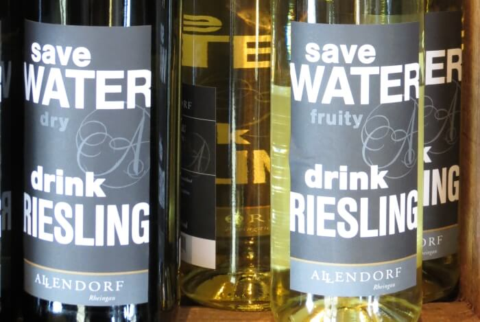 On a Rudesheim Wine Time wine tasting tour in Germany, Save Water Drink Reisling bottles at the Allendorf wine shop