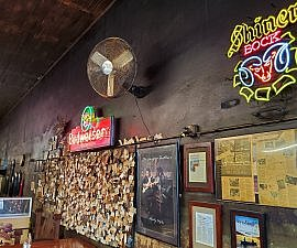 Smoky wall of beer signs and business cards Louie Mueller BBQ Taylor TX near Austin (photo by Sheila Scarborough)