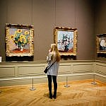 art museum woman looks at paintings